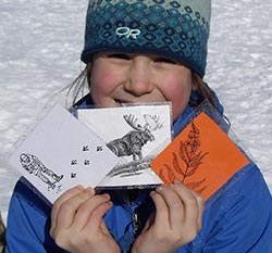 Girl in the snow holding educational materials